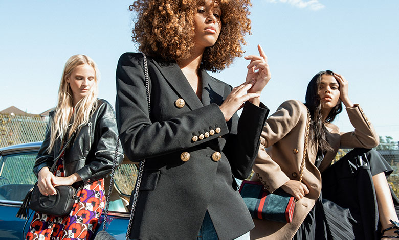 Three female models next to a ventage car wearing a Giuseppe Zanotti leather jacket, a floral Marni dress, a Balmain blazer with jeans, and a velvet Gucci cap, Valentino pleated skirt and camel Victoria Beckham over coat