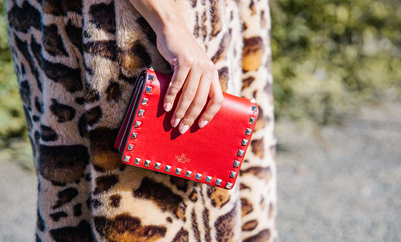 A model wearing a faux fur leopard print Dolce & Gabbana coat and a a red studded Valentino bag