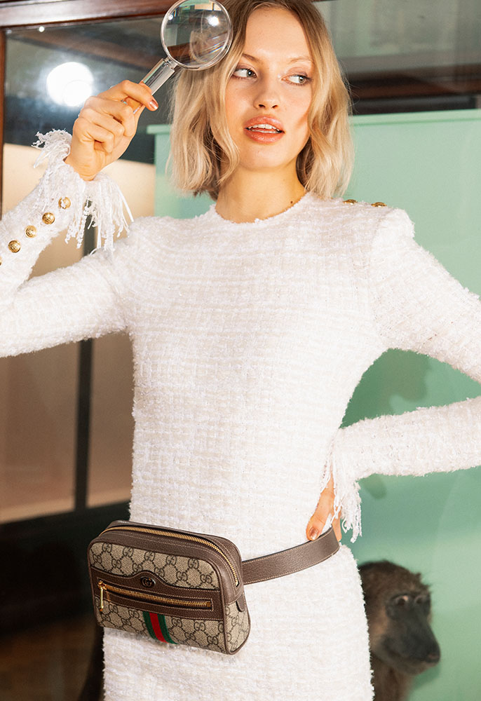 A female model wearing a white tweed knitted Balmain dress with gold shoulder epaulettes and gold buttons on the cuff with a Gucci Ophidia belt bag in beige monogrammed canvas around her waist. She is holding a magnifying glass to her eye and is in a museum.