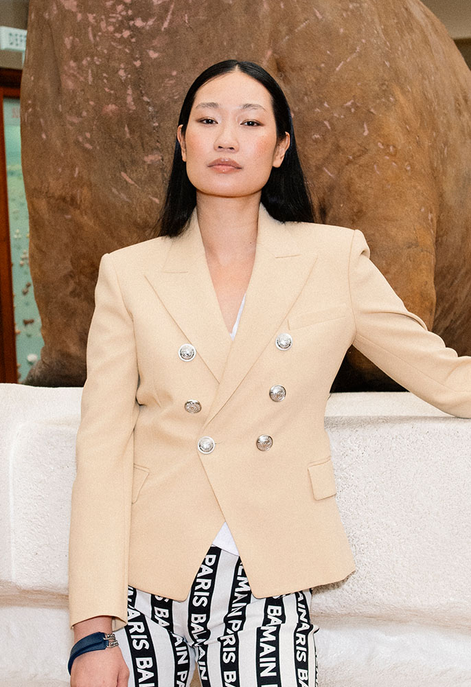 A female model wearing a light beige Balmain double breasted blazer with silver buttons and black and white striped logo Balmain trousers, stood in front of a taxidermy walrus at the museum