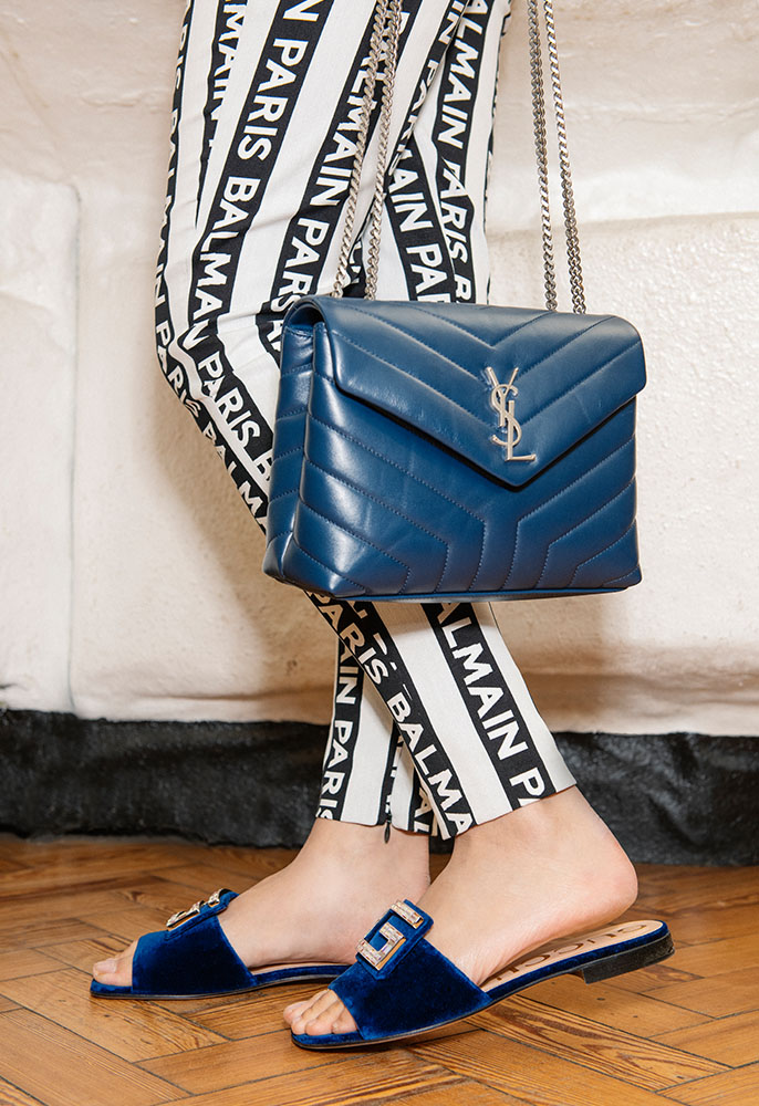 A female model wearing black and white striped Balmain logo trousers, midnight blue velvet Gucci sliders with a crystal G logo and a navy leather quilted Saint Laurent bag with a YSL clasp