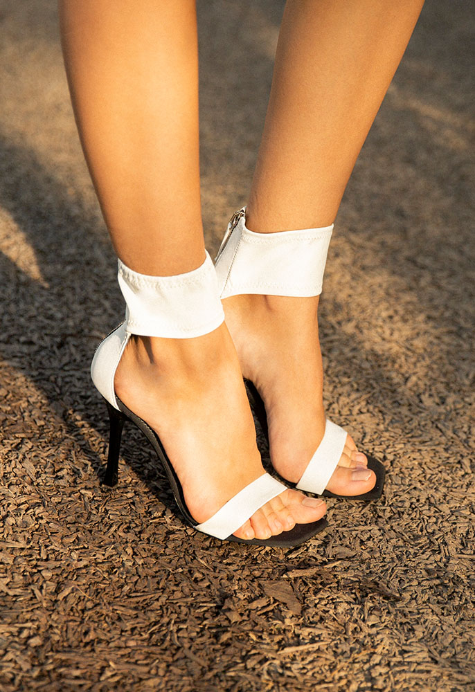 A photograph of a female model's feet wearing white leather Giuseppe Zanotti ankle strap heeled sandals with an open toe and black stiletto heel