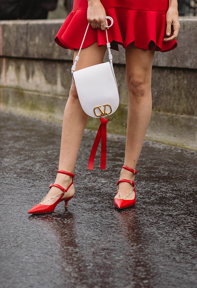 A woman at Paris fashion week wearing a red mini dress and red pointed strappy kitten heels with a white Valentino bag