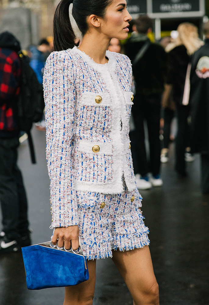 A woman at Paris fashion week wearing a Balmain tweed double breasted blazer and matching shorts in white, cream, blue and pink