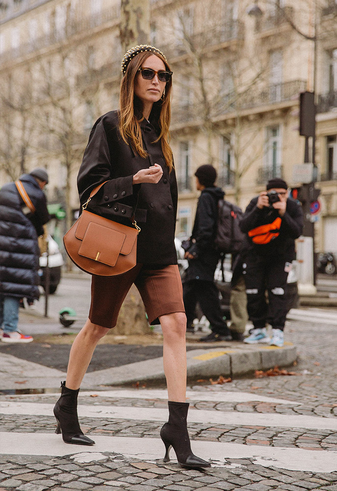 A woman at Paris Fashion Week wearing brown tailored midi shorts, a black double breasted jacket, black pointed sock boots, a tan leather bag and a pearl-studded Prada headband