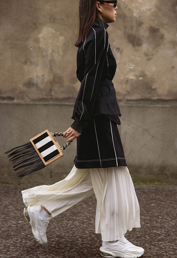 A woman at Paris Fashion week wearing white wide leg pleated trousers with white Valentino Bounce trainers, a black long-line jacket with white ribbing and a black and white stripe box bag with black leather tassels