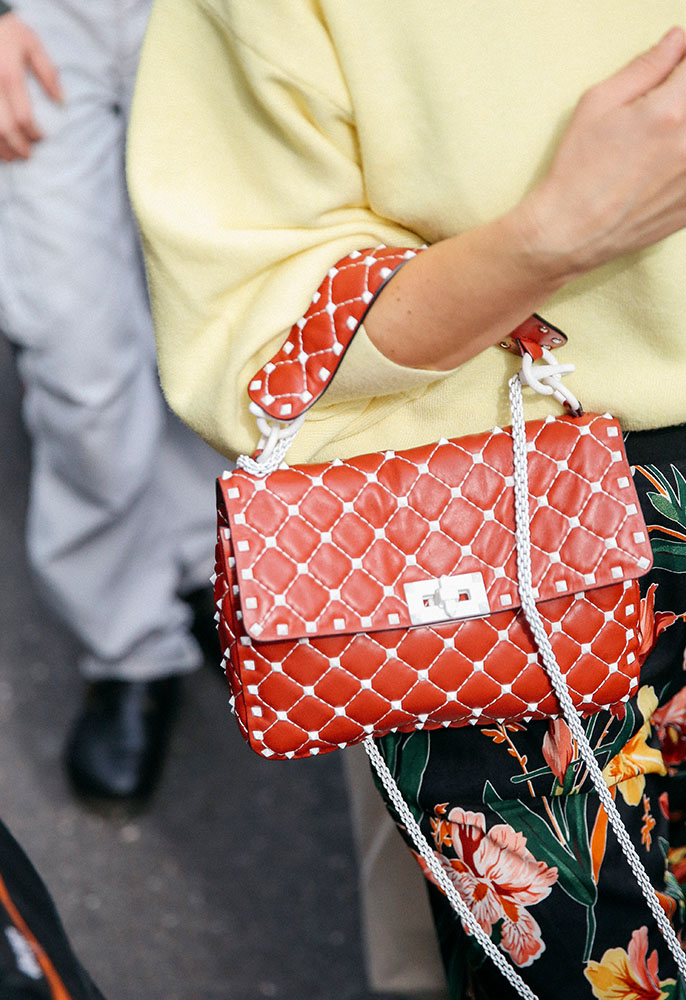 Woman at London Fashion Week with a white stud Valentino Rockstud bag in orange leather