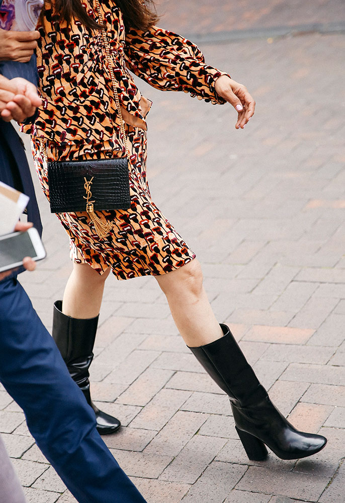 Woman at London Fashion week wearing a printed dress, block heel knee-high boots and a Saint Laurent bag