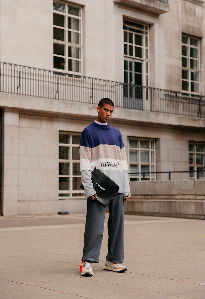 A male model wearing Off-White tailored trousers, an Off-White logo knitted jumper, Off-White trainers and holding an Off-White black leather portfolio case