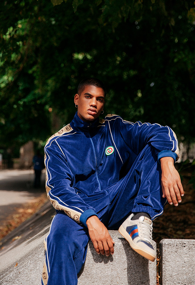 A male model wearing a blue velour Gucci tracksuit and track top with beige GG stripes down the arms and legs and a pair of Gucci retro-inspired trainers