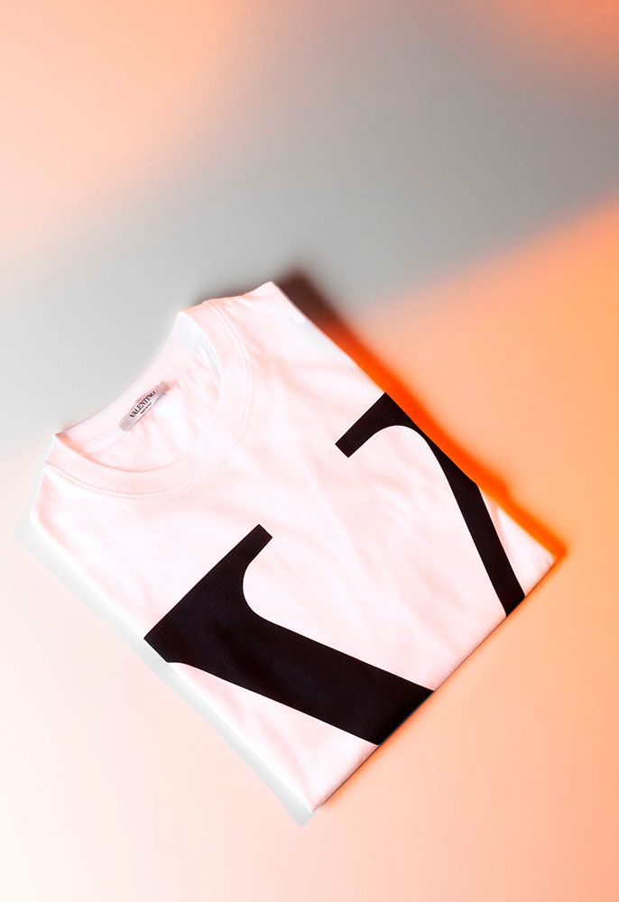 A folded white Valentino T-shirt with a black graphic VLOGO on the front