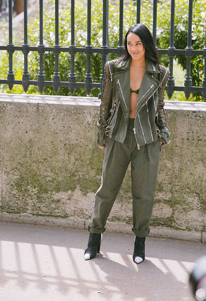 A woman posing outside the Balmain show in Paris wearing khaki trousers and jacket and black pointed boots