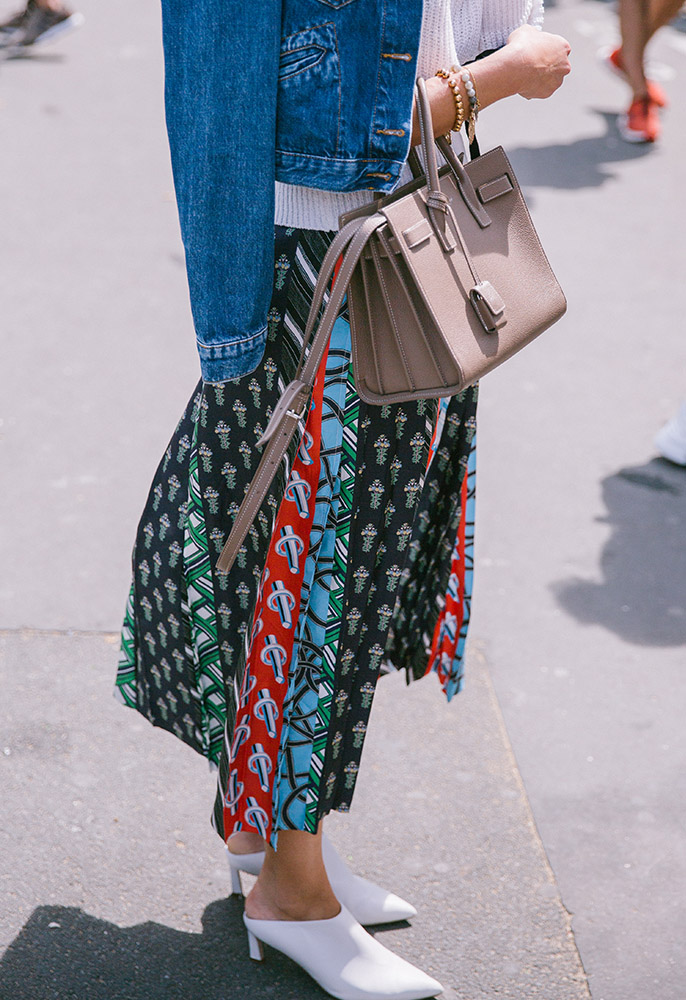 A woman at Paris Fashion Week Men's wearing a printed, pleated skirt, a denim jacket, white pointed mules and a Saint Laurent Sac de Jour bag