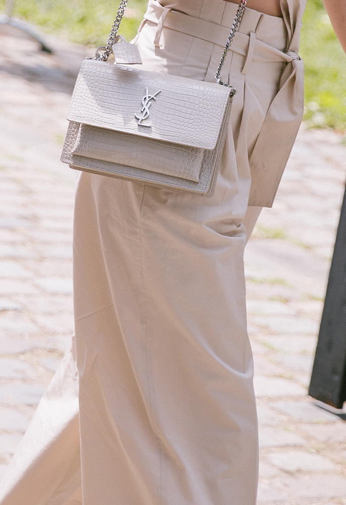 A woman at Paris Fashion Week Men's wearing taupe culottes and a Saint Laurent Sunset crocodile bag