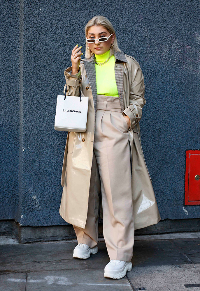 A London Fashion Week attendee wearing a neon green turtle neck jumper, a beige patent trench coat, beige wide leg trousers, a white Balendiaga bag and white chunky traienrs