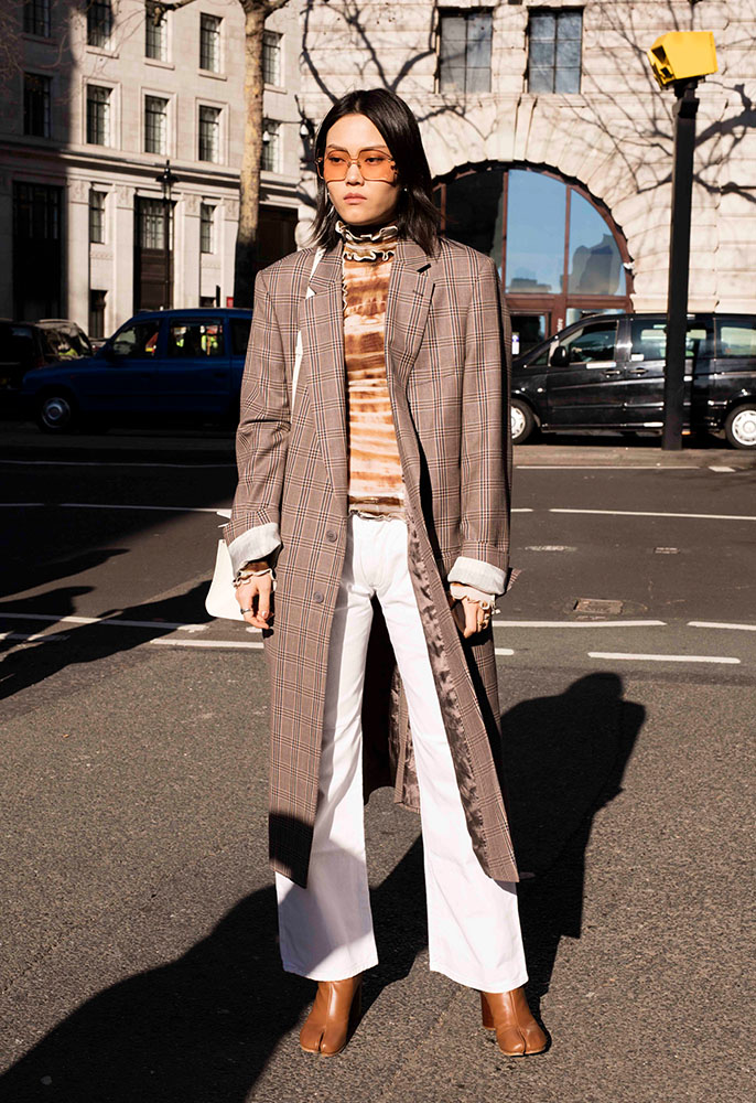 A guest at London Fashion Week wearing white flared jeans, brown leather boots, a tie-dye brown and white high neck blouse, a brown checked formal coat and a white leather shoulder bag