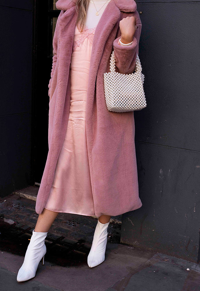 A guest at London Fashion Week wearing a pink slip dress over a white Tee, a pink long-line fluffy coat, white leather pointed boots and a small white beaded bag
