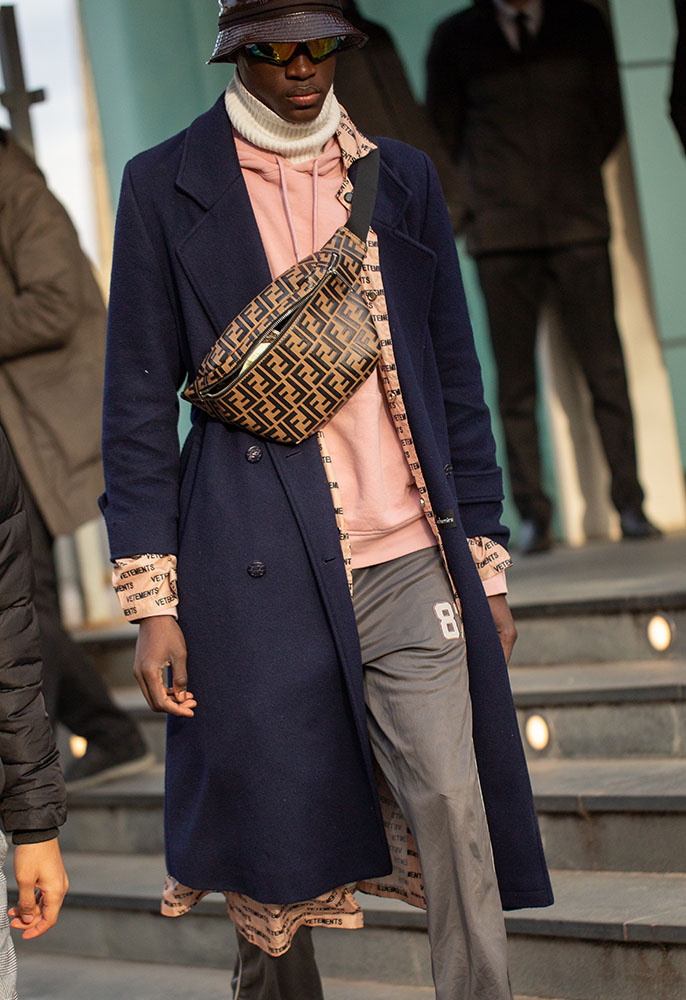 Photograph of a man on the streets of Paris wearing a leather bucket hat and brown Fendi logo Zucca belt bag strapped across his chest, a pink hoodie with a white rollneck under it, grey track pants and a navy formal longline coat