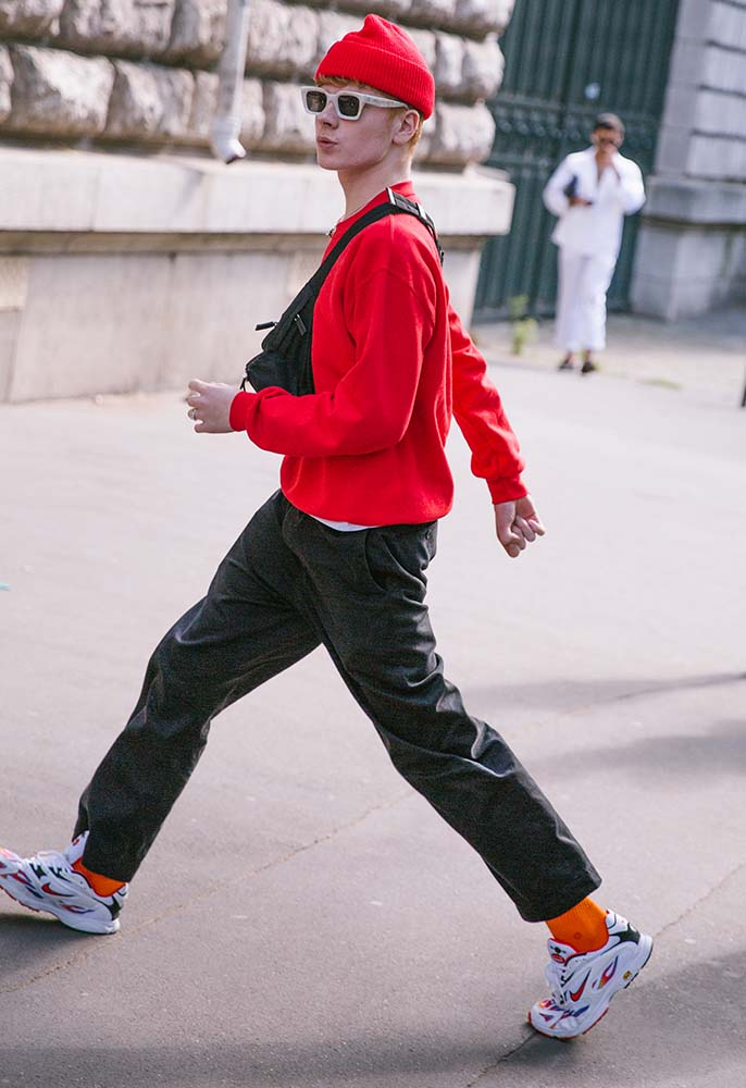 Streetwear icon Gully wearing trainers, woolen trousers, a red sweathsirt and beanie and a cross body bag