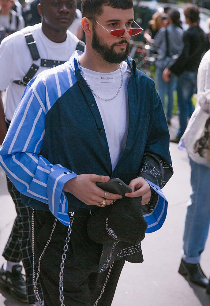 A man at Paris Fashion Week men's wearing a blue striped ubottoned shirt and white Tee, Balenciaga cap and black trousers with chains