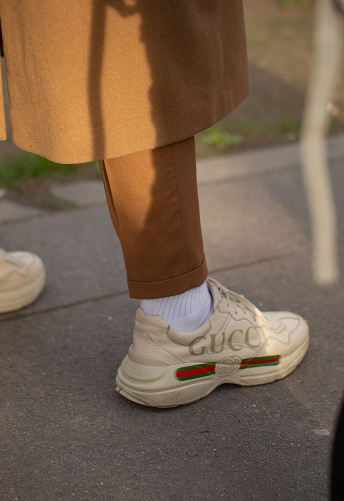 A man at Paris Fashion Week Men's wearing Gucci Rhyton runner trainers with the 'fake' logo