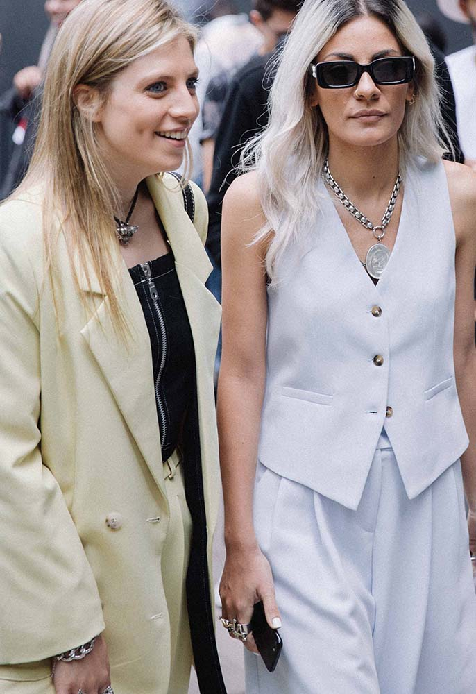Two London Fashion Week Men's attendees wearing an overszied blazer and matching suit trousers with a black zip-front bralet and a waistcoat two-piece with horn buttons