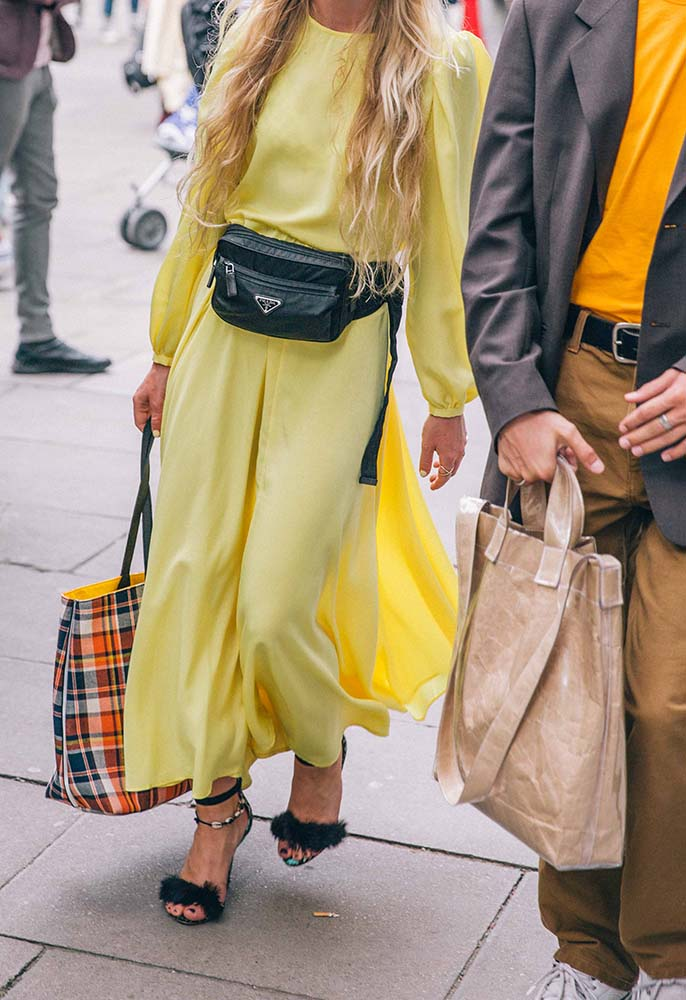 A London Fashion Week Men's attendee wearing a yellow silk maxi dress with bell sleeves, a Prada sport black leather bum bag, black heeled sandals and carrying a checked tote bag