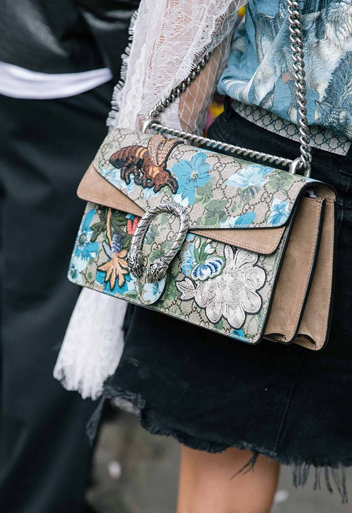 A London Fashion Week attendee wearing a black denim midi skirt with a Gucci belt, a printed blue jacket with lace sleeves and a blue and taupe embelished Gucci Dionysus handbag