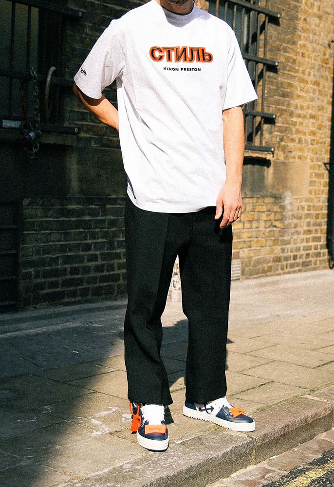Model wearing Heron Preston Satin CTNMB T Shirt, Valentino Logo Trousers, and Off-White Off Court High Top Trainers