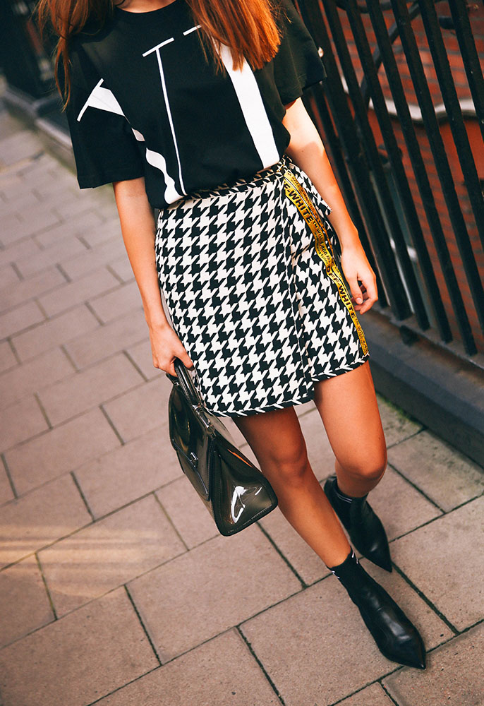 Model wearing Valentino Logo T Shirt, Off-White Houndstooth Mini Skirt, Fendi Nappa Sock Boots, and Dolce & Gabbana Sicily Semi Transparent Rubber Bag