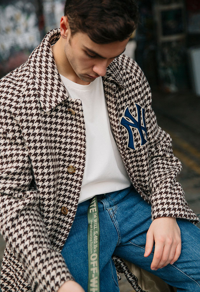 A male model wearing a checked Gucci New York Yankees tailored coat, straight leg jeans, a white T-shirt and Off-White industrial belt