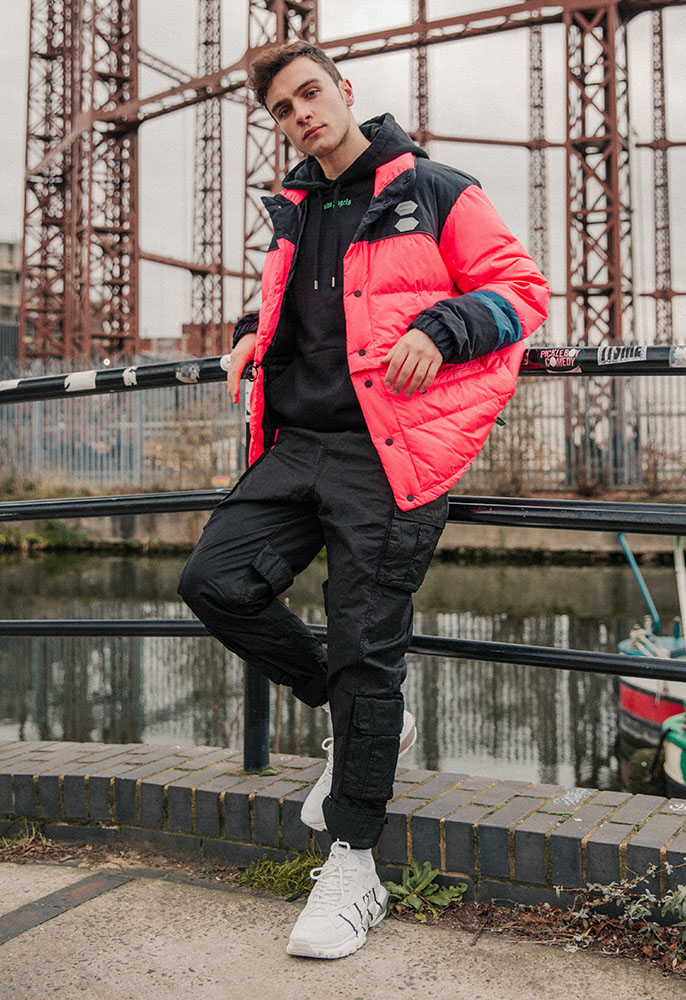 Model wearing a pink Off-White puffer coat and black cargo track pants with Valentino VLTN bounce logo trainers