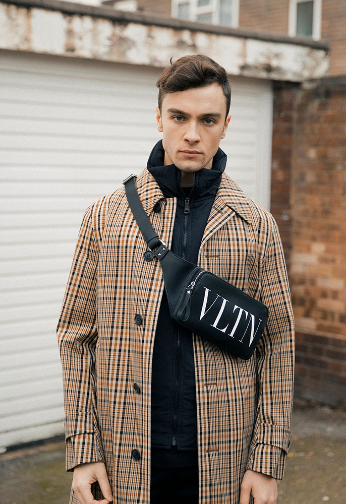 A male model wearing a checked Burberry car coat over a black zip-up Valentino track top with a black leather Valentino belt bag strapped across his chest