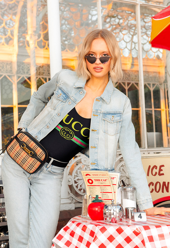 A female model wearing a matching pair of Off-White bleached, distressed denim jeans and jacket with a Gucci logo swimsuit underneath, a Burberry check belt bag and a pair of heart shaped Saint Laurent sunglasses