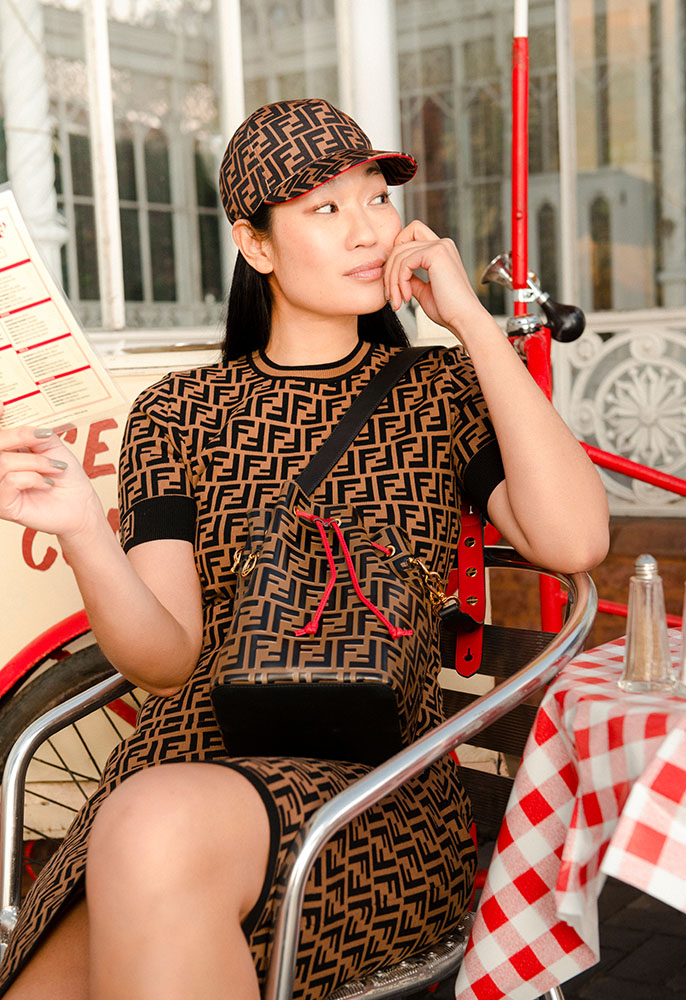 A female model sat on a cafe chair in front of an icecream bike wearing a brown and black Fendi FF logo knitted dress and matching cap and leather bucket bag