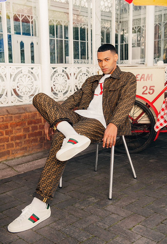 A male model sat on a cafe chair in front of an icecream bike wearing a matching Fendi brown FF logo denim jacket and jeans, a white Valentino Tee with a red V logo and a pair of white Gucci trainers
