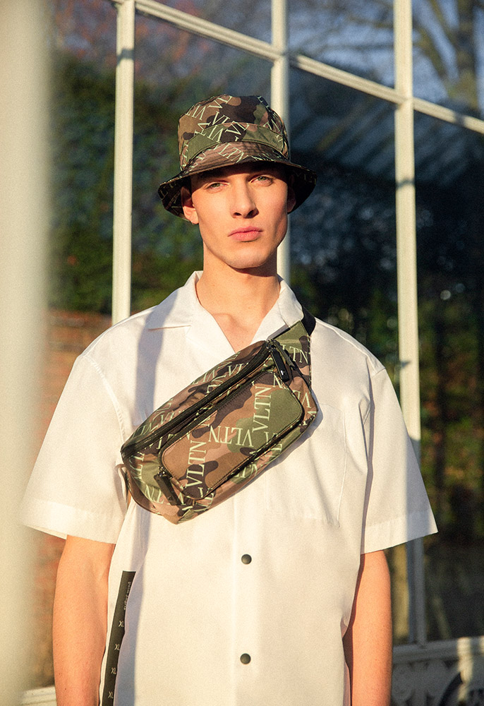 A model wearing a white Palm Angels bowling shirt and a camouflage logo Valentino bucket hat with a camo Valentino belt bag strapped across his chest