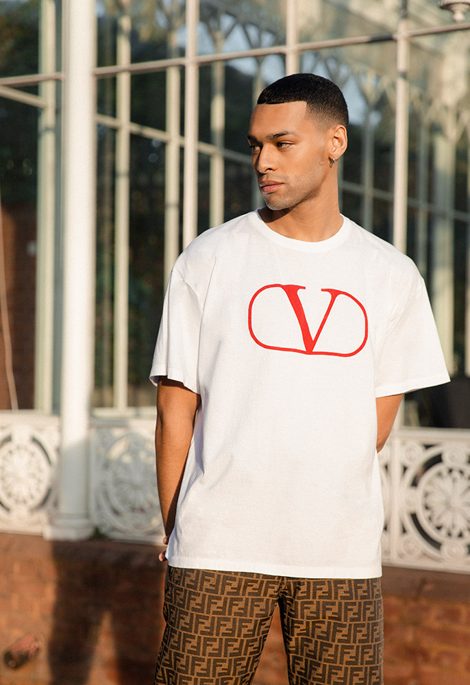 A male model in the sun wearing a white Valentino T-shirt with a large graphic V logo on the front