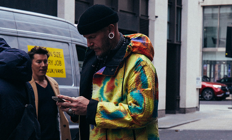 London Fashion Week Men's showgoers wearing beanie and oversize multicoloured coat