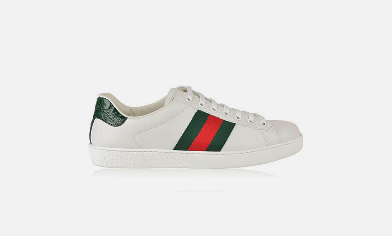 A white leather Gucci New Ace trainer with a green mock alligator heel tab, white laces and a green and reg Gucci Web stripe down the centre of the quarter panel