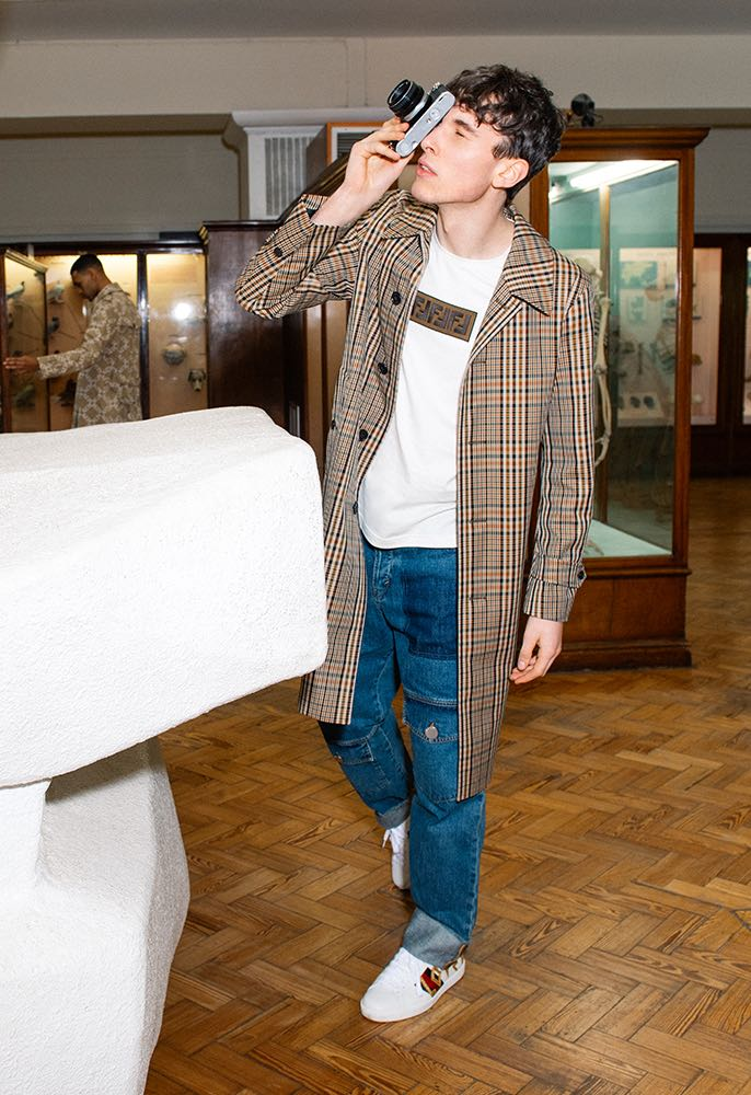 A male model wearing a checked Burberry car coat with a white Fendi logo T-shirt with workwear-inspired JW Anderson Jeans and Gucci trainers embroidered with the word Love, taking a picture in a museum