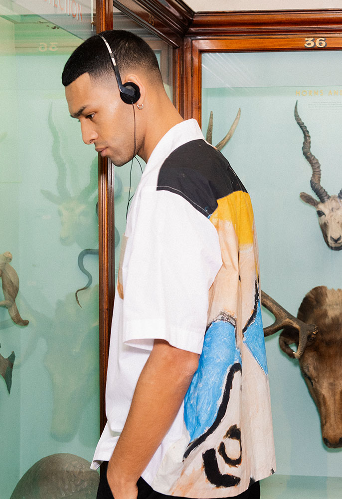 A male model looking into a glass cabinet at a museum whilst listening to a headset wearing a white, black, yellow and blue abstract printed shirt by Marni