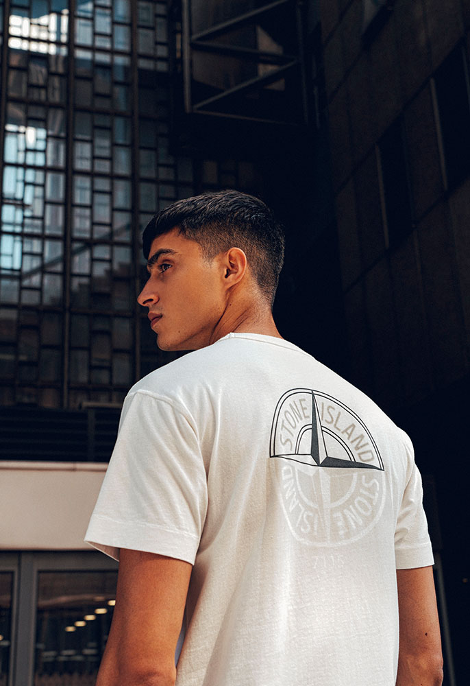A male model with his back to the camera wearing a white Stone Island crew neck T-shirt with a large Stone Island logo on the back