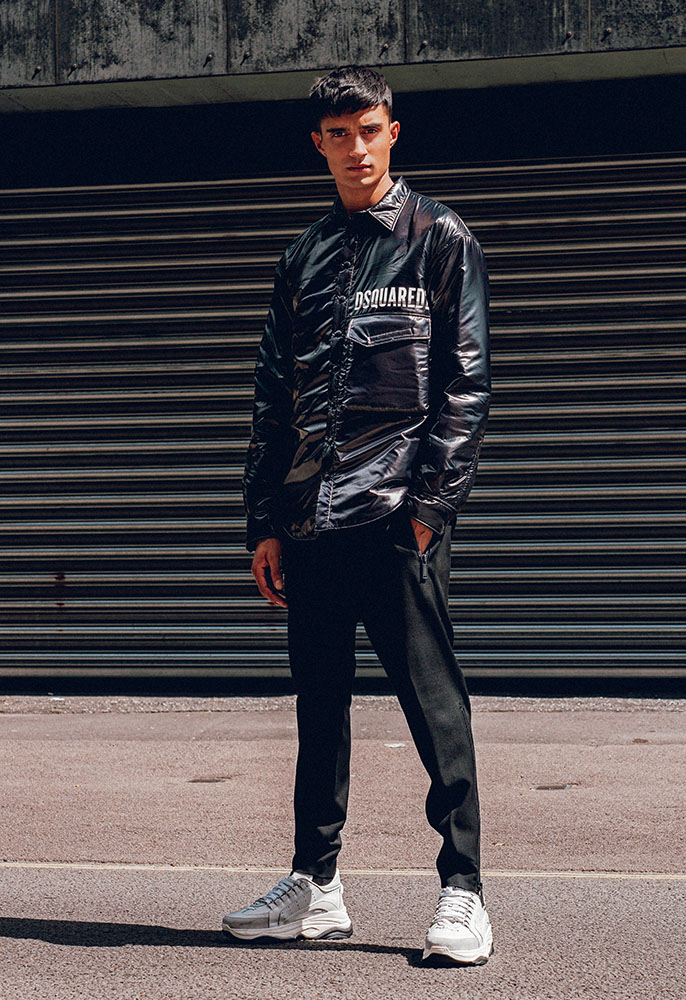A male model wearing a black Dsquared2 button down coach jacket, black trousers and white chunky Dsquared2 trainers