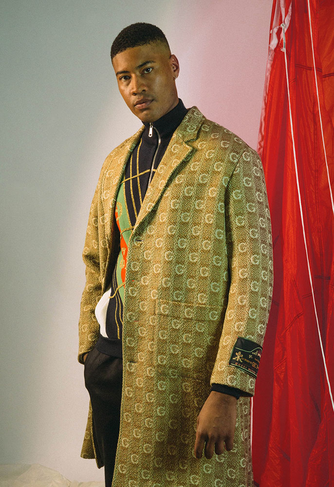A male model wearing a black, gold, red and green knit zip-through cardigan with black track pants and an all-over GG woven coat