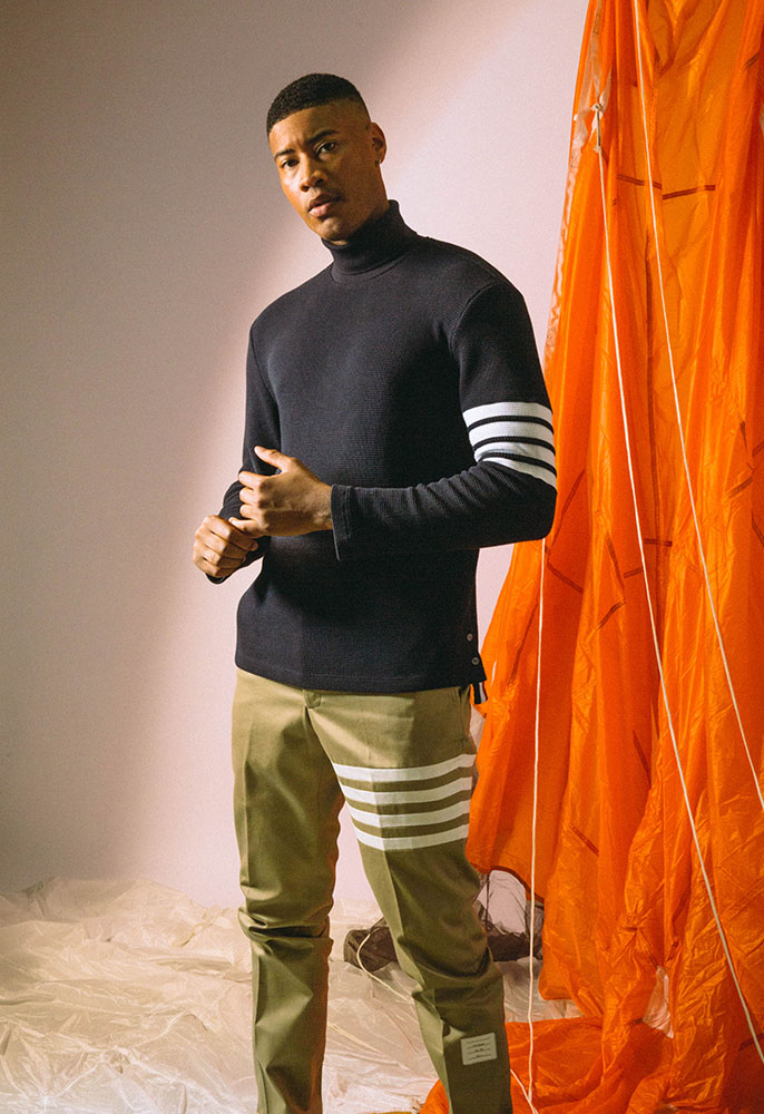 A male model wearing a navy Thome Browne roll neck jumper with white stripes on the arm and camel Thom Browne trousers with white stripes around the leg