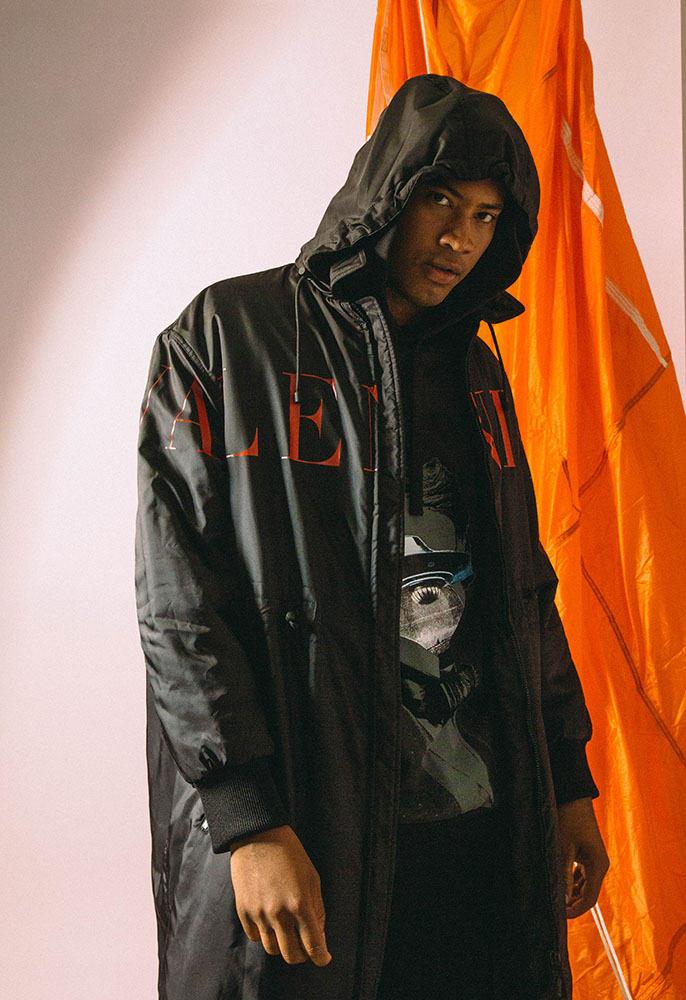 A male model wearing a black Valentino logo longline raincoat with the hood up and a UFO printed Valentino sweatshirt underneath