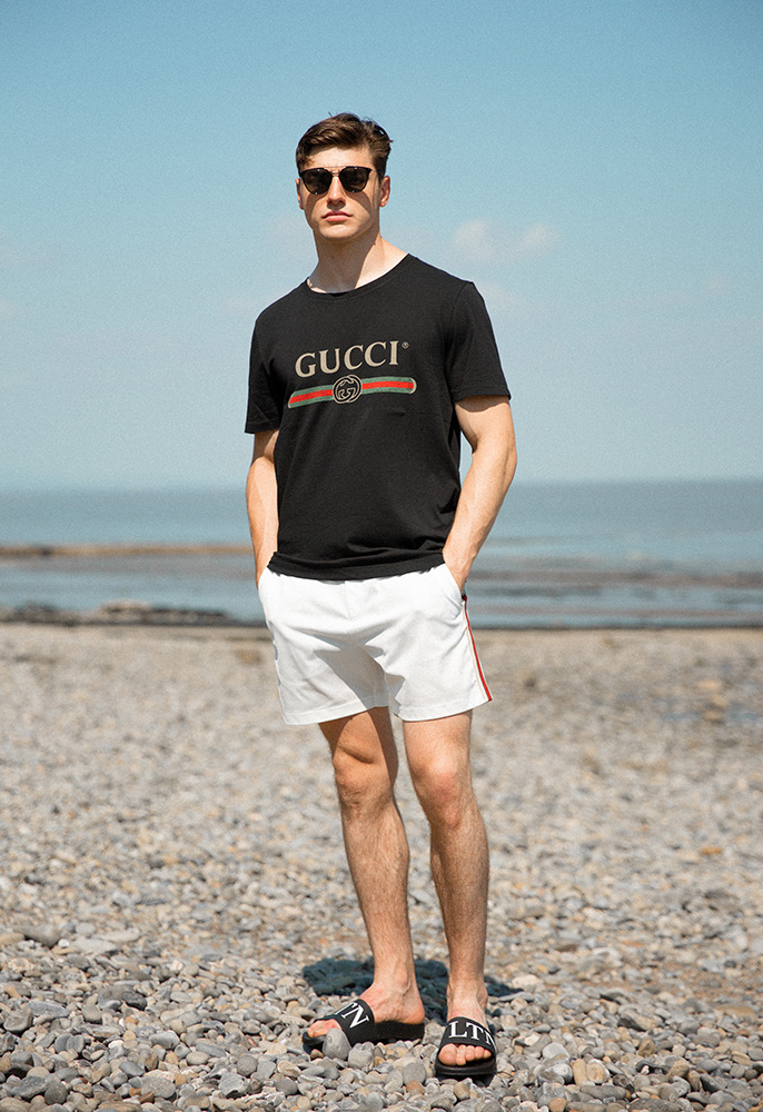 Model on a beach wearing Gucci T-shirt and shorts and Valentino sliders