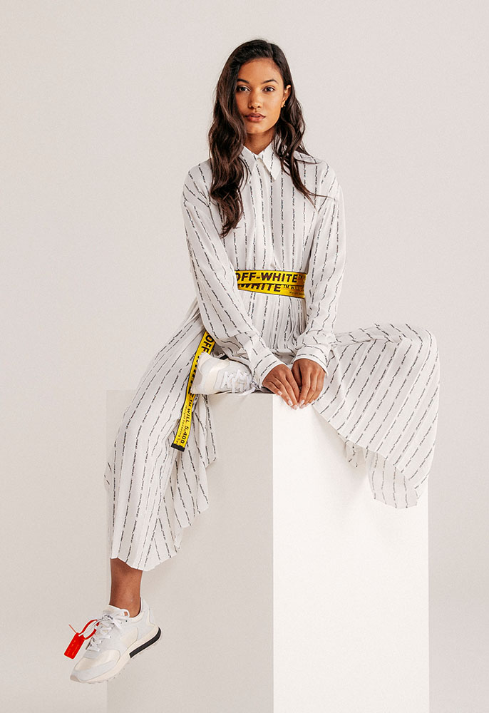 A woman wearing a matching white Off-white logo top and culottes, a yellow Off-White industrial belt and Off-White blue and white arrow trainers