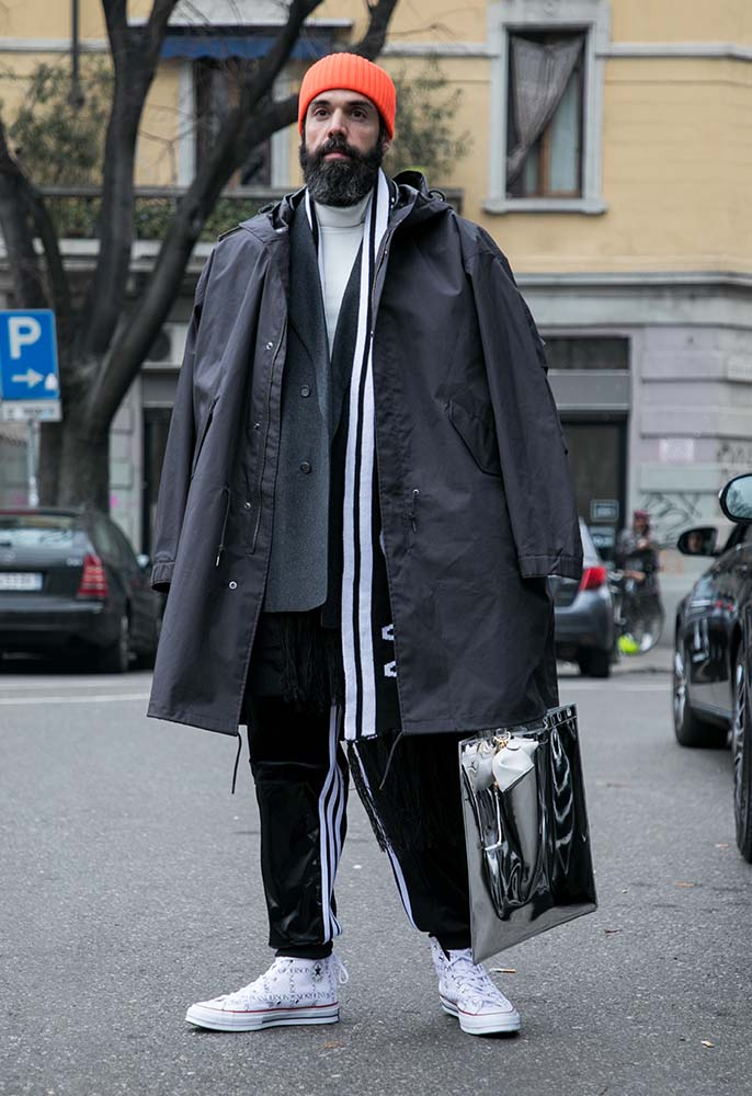 Man on the street wearing an oversized layered anorak, tracksuit pants, sweatshirt and scarf